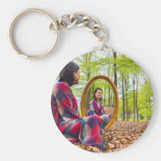 Woman sits with mirror in forest during spring basic round button keychain