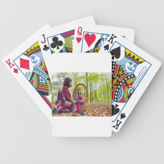 Woman sits with mirror in forest during spring bicycle playing cards