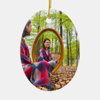 Woman sits with mirror in forest during spring ceramic oval ornament
