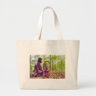 Woman sits with mirror in forest during spring large tote bag