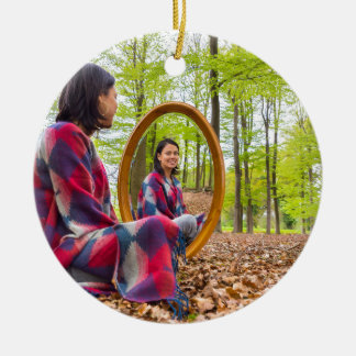 Woman sits with mirror in forest during spring round ceramic ornament