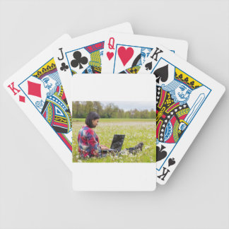 Woman sitting with laptop in spring meadow bicycle playing cards