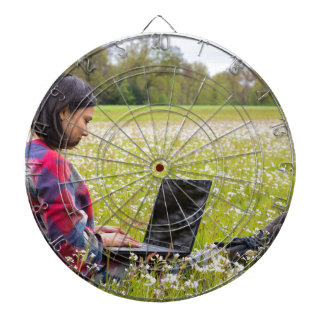 Woman sitting with laptop in spring meadow dartboard