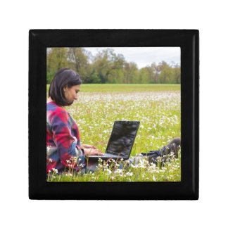 Woman sitting with laptop in spring meadow gift box