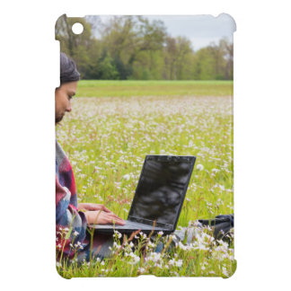 Woman sitting with laptop in spring meadow iPad mini cover
