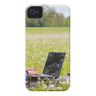 Woman sitting with laptop in spring meadow iPhone 4 cover