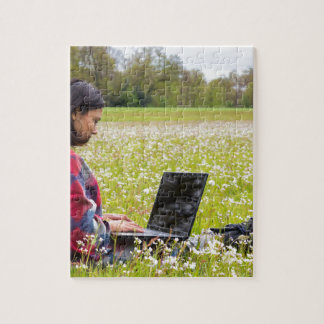 Woman sitting with laptop in spring meadow jigsaw puzzle