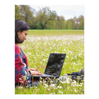 Woman sitting with laptop in spring meadow letterhead