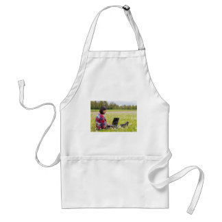 Woman sitting with laptop in spring meadow standard apron