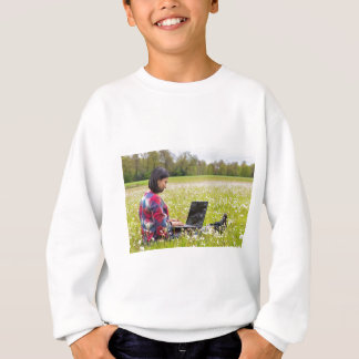 Woman sitting with laptop in spring meadow sweatshirt