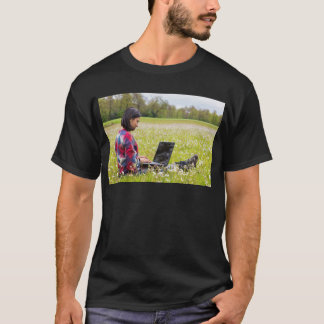 Woman sitting with laptop in spring meadow T-Shirt