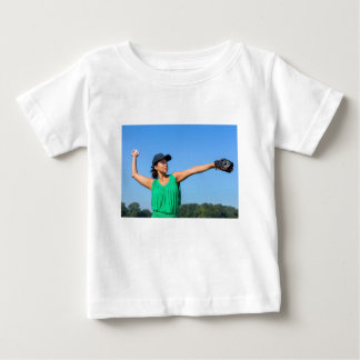 Woman with glove and cap throwing baseball outside baby T-Shirt