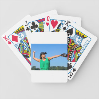 Woman with glove and cap throwing baseball outside bicycle playing cards