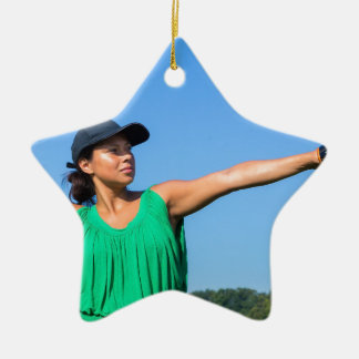 Woman with glove and cap throwing baseball outside ceramic star ornament