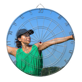 Woman with glove and cap throwing baseball outside dartboard