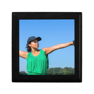 Woman with glove and cap throwing baseball outside gift box