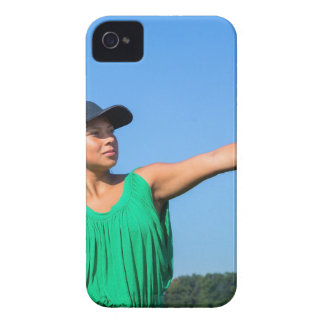 Woman with glove and cap throwing baseball outside iPhone 4 cases