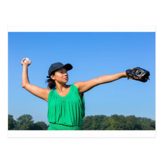 Woman with glove and cap throwing baseball outside postcard