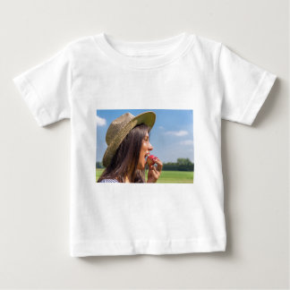 Woman with hat eating red apple outside baby T-Shirt