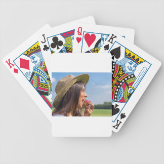 Woman with hat eating red apple outside bicycle playing cards