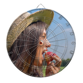 Woman with hat eating red apple outside dartboard