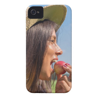 Woman with hat eating red apple outside iPhone 4 cases
