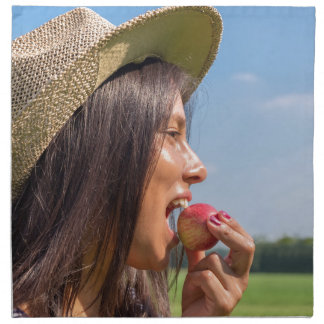 Woman with hat eating red apple outside napkin