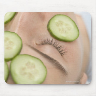 Woman with slices of fresh cucumber on her face, mouse pads