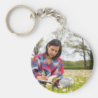 Woman writing in meadow with spring flowers basic round button keychain
