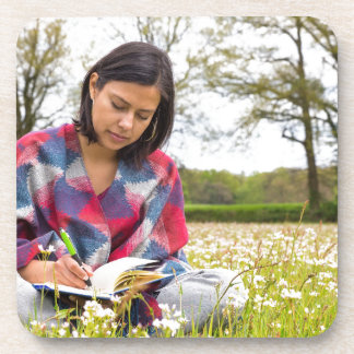 Woman writing in meadow with spring flowers beverage coaster