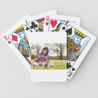 Woman writing in meadow with spring flowers bicycle playing cards