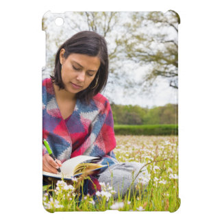 Woman writing in meadow with spring flowers iPad mini case
