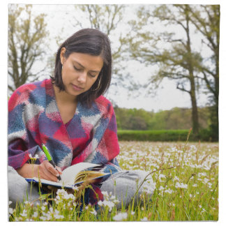 Woman writing in meadow with spring flowers napkin