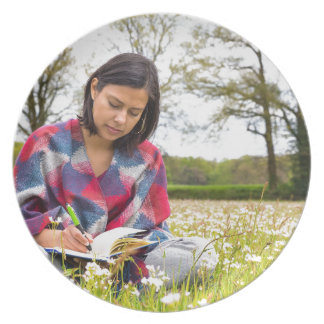 Woman writing in meadow with spring flowers party plates