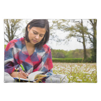 Woman writing in meadow with spring flowers placemat