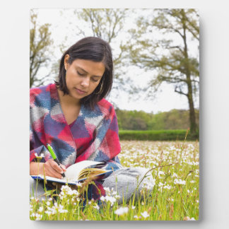 Woman writing in meadow with spring flowers plaque