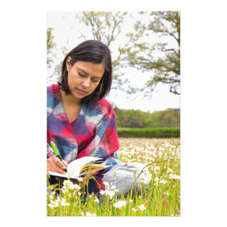 Woman writing in meadow with spring flowers stationery design