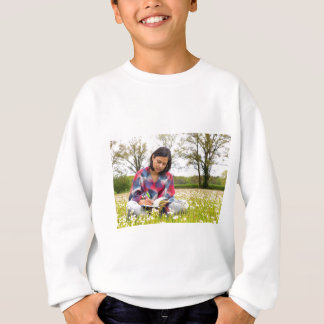 Woman writing in meadow with spring flowers sweatshirt