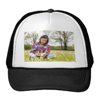 Woman writing in meadow with spring flowers trucker hat