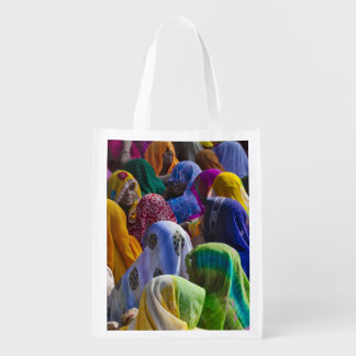 Women in colorful saris gather together grocery bags
