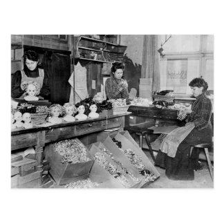 Women making wigs for dolls postcard