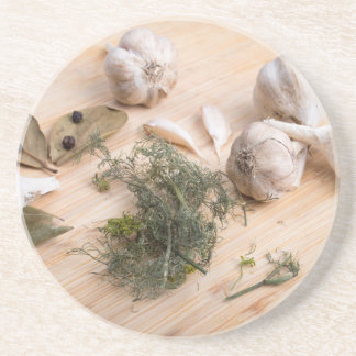 Wooden board with garlic and dried spices closeup coaster