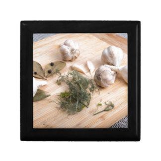 Wooden board with garlic and dried spices closeup gift boxes