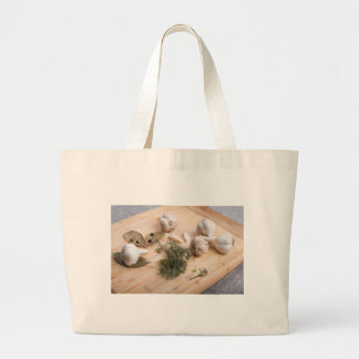 Wooden board with garlic and dried spices closeup large tote bag