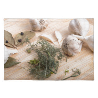 Wooden board with garlic and dried spices closeup placemat