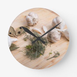 Wooden board with garlic and dried spices closeup round clock