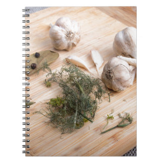 Wooden board with garlic and dried spices closeup spiral notebook