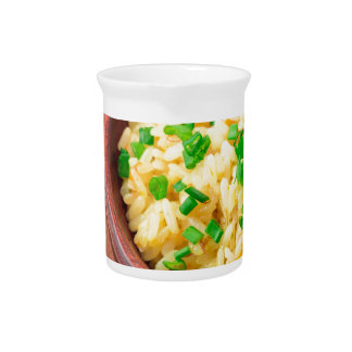 Wooden bowl of cooked rice and vegetables pitcher