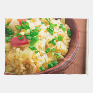 Wooden bowl of cooked rice and vegetables towel
