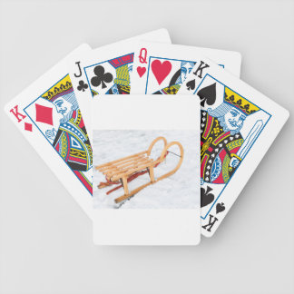Wooden children sled in winter snow bicycle playing cards